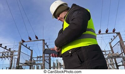 Electrician engineer using tablet near substation and...