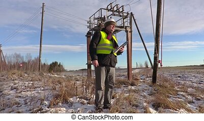 Electrician engineer talking near power lines and...