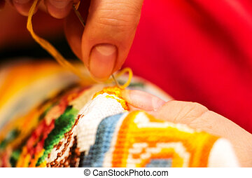 The cross stitching. Photo of woman hands closeup, which...