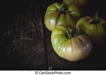 Green RAF tomatoes - Green unripe big RAF tomatoes over old...