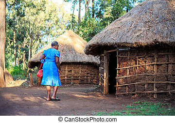 African woman entering a traditional Kenyan house - African...