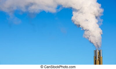 White smoke rising from smokestacks into the blue sky....