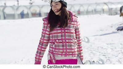 Cute and happy female asian snowboarder walking with her...