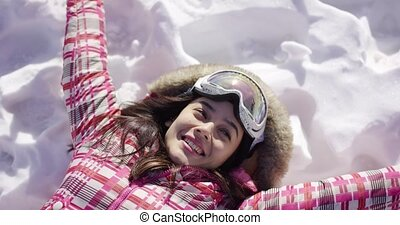 Young woman lying on snow with ski goggles - Half body...