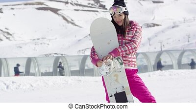 Pretty young asian woman holding snowboard