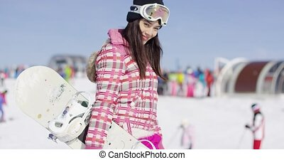 Young smiling woman with ski boots on the piste with goggles...