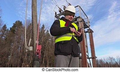 Electrician engineer using tablet near power lines and...