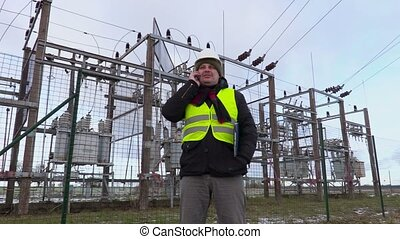 Electrician engineer talking on smart phone near substation...