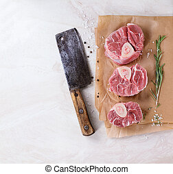 Raw osso buco meat on crumpled paper with salt, pepper and...