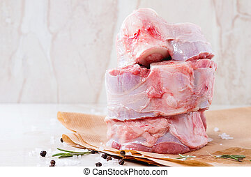 Raw osso buco - Stack of raw osso buco meat on crumpled...