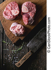 Raw osso buco meat on wooden cutting board with vintage...
