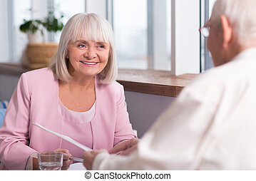 Pretty senior businesswoman smiling at her colleague -...