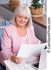 Enthusiastic senior lady studying the report - I like those...