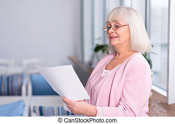 Professional elderly woman reading a document