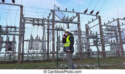 Electrician engineer walking and using smart phone near...