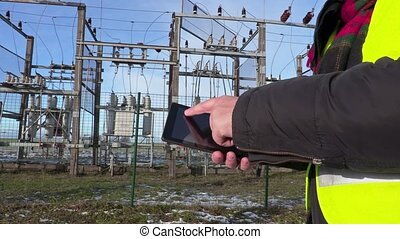 Electrician engineer using tablet near substation close up