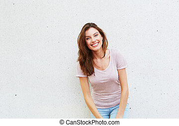 beautiful young lady standing against white wall and smiling...