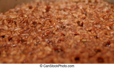 Red rice is boiling in a pot of water.