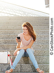 attractive young lady sitting on steps and using mobile phone