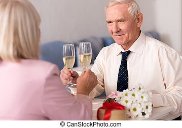 Attentive senior man toasting his ladys beauty - To the love...