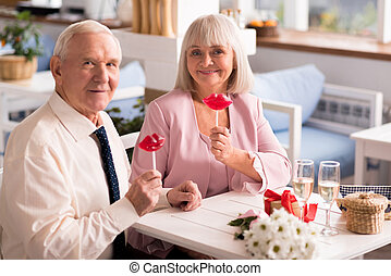 Charming senior couple posing with candies - These look...