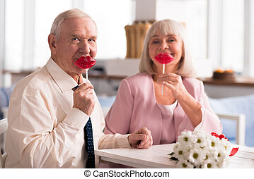 Adorable elderly couple holding up red lollipops - This is...