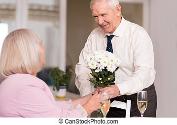 Gallant handsome man giving flowers - Flowers for her. Grey...