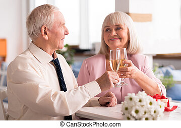 Two lovely elderly people holding up glasses of champagne -...