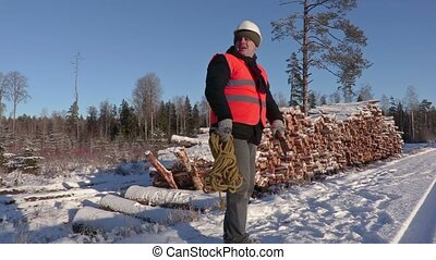 Lumberjack with rope and ax calling other workers and...