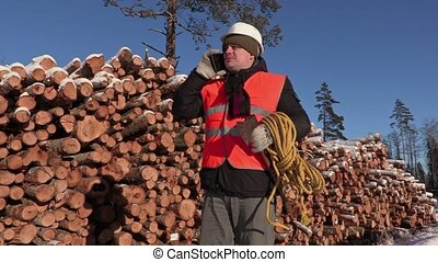 Lumberjack with rope and ax talking on phone near pile of...