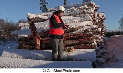Lumberjack take pictures on phone near pile of logs in...
