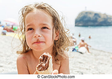 Little boy eating an ice cream on the beach