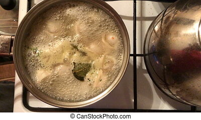 Dumplings cooked in a pot on a gas stove top view