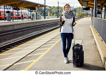 Woman With Luggage And Coffee Cup Waiting At Train Station -...
