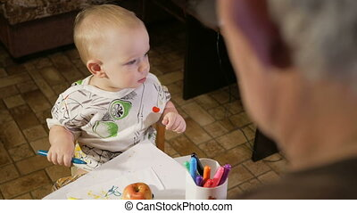 Grandfather with his grandson kid draws markers on paper. The boy looks carefully and help. Smiling and surprised. The concept of teaching children at home