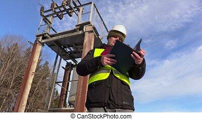 Electrician engineer talking near transformer