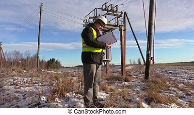 Electrician engineer checking documentation near transformer