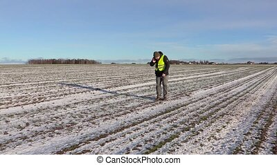 Farmer on field of snow covered plants