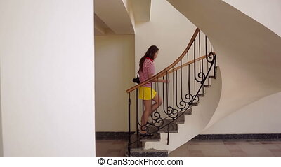 beautiful girl walks up the stairs with a camera.