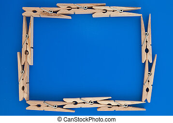 Frame made of wooden clothes pegs on a blue background.