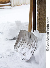 Snow shovel in snowed front yard - Snow shovel in a snowed...