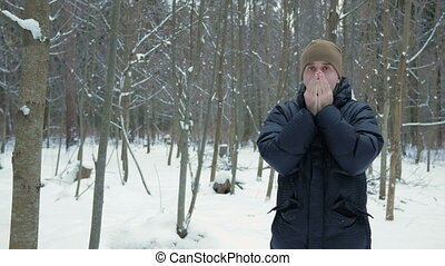 A young man in winter forest freeze. He's breathing on his hands, rubs and wears a hood jackets.