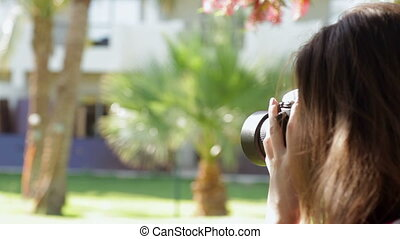 beautiful woman walking in the park and take pictures.
