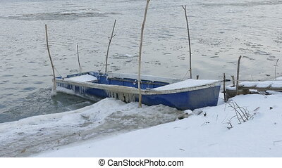 Boat at river in winter with ice and snow