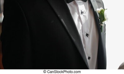 Beautiful wedding details.Black suit, white shirt and...