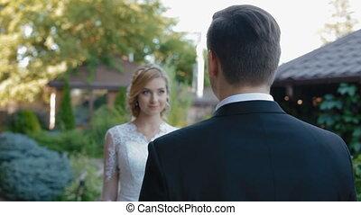 Bride comes to groom and wink - Happy bride comes to groom,...