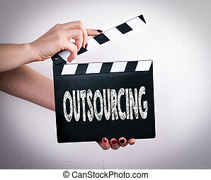 Outsourcing. Female hands holding movie clapper. Gray...