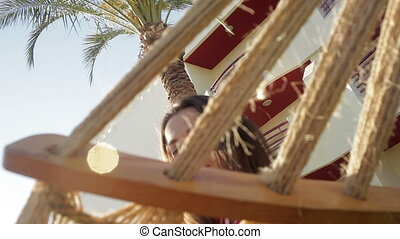woman in striped T-shirt sitting in a hammock - woman in a...