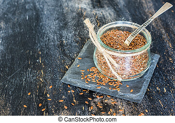 Organic food concept with flax seeds on dark wooden...