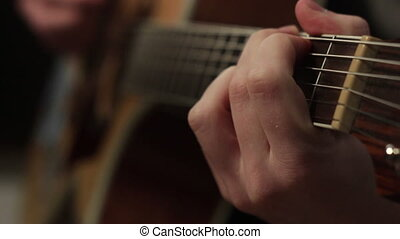 playing on the acoustic guitar. Musical instrument with guitarist hands